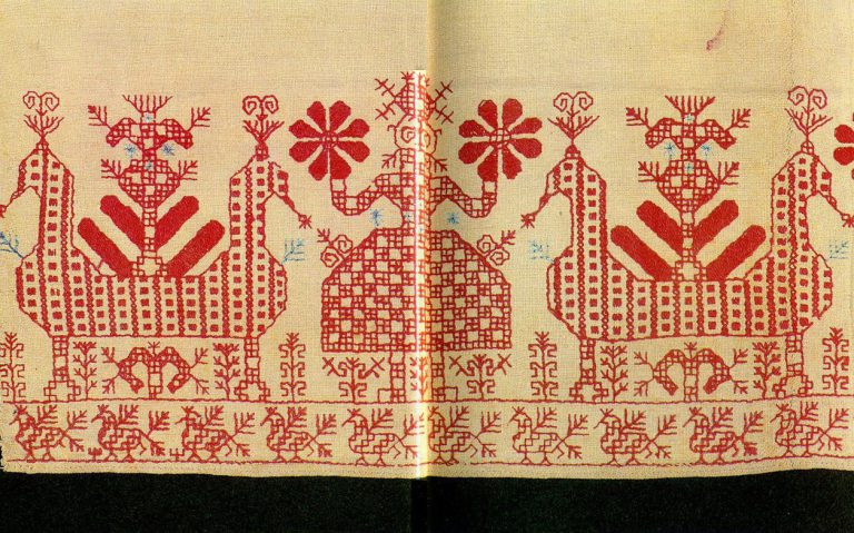 """Maiden"" and ""sun chariots"" with birds on an ornamental panel from the hem of a woman's shirt. <br/>Second half of   19th century"