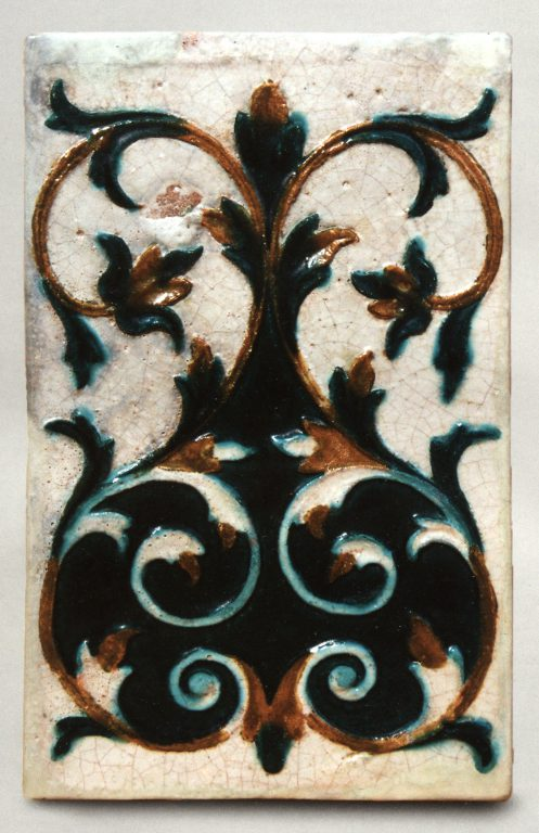 Multicoloured wall tile with floral  relief ornament. <br/>First half of 18th century