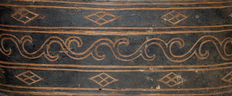 Коробочка овальной формы с крышкой, чёрного цвета, покрытая орнаментом. Фрагмент